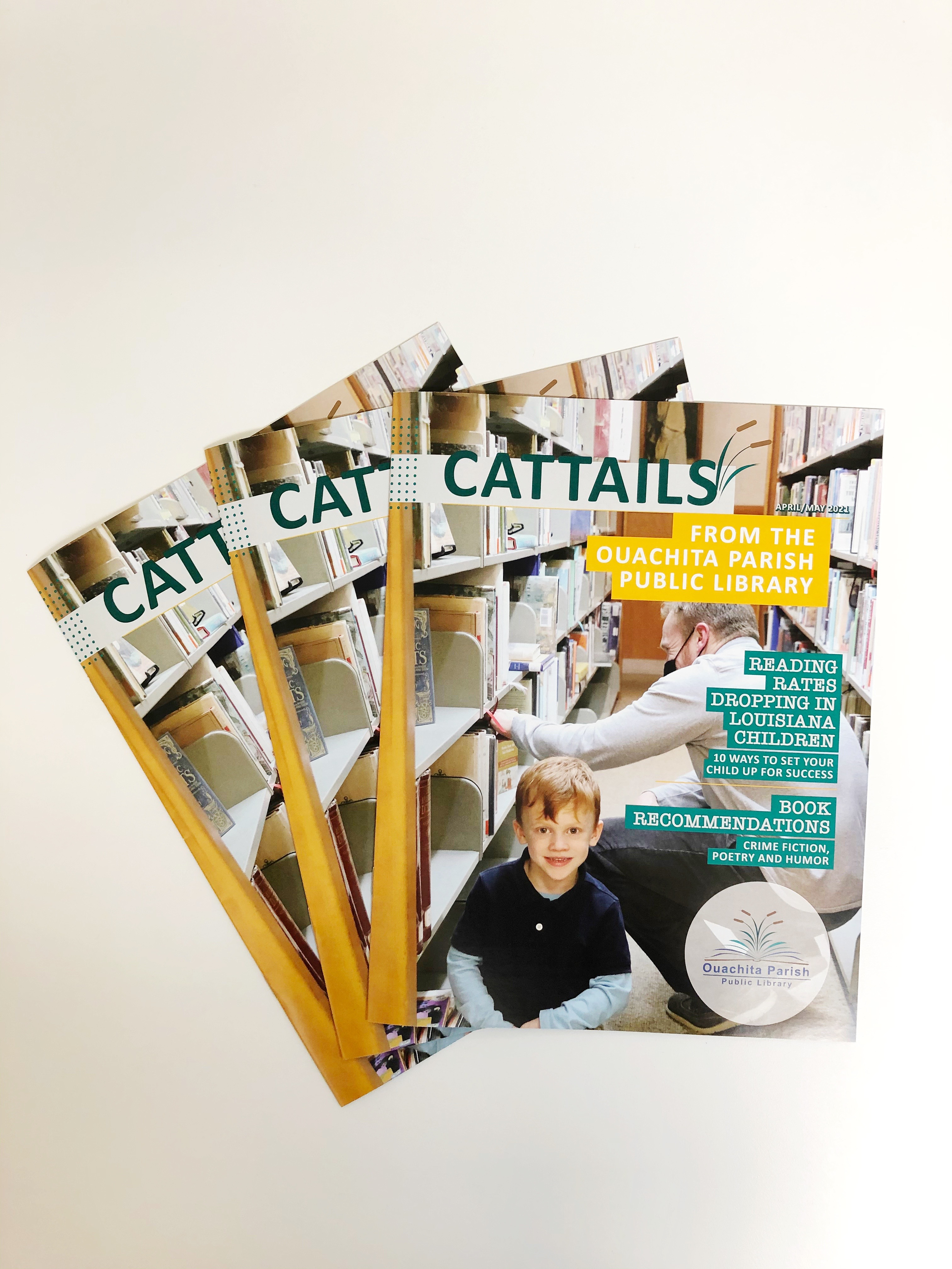 Three issues of the April/May Cattails lay on a white table.