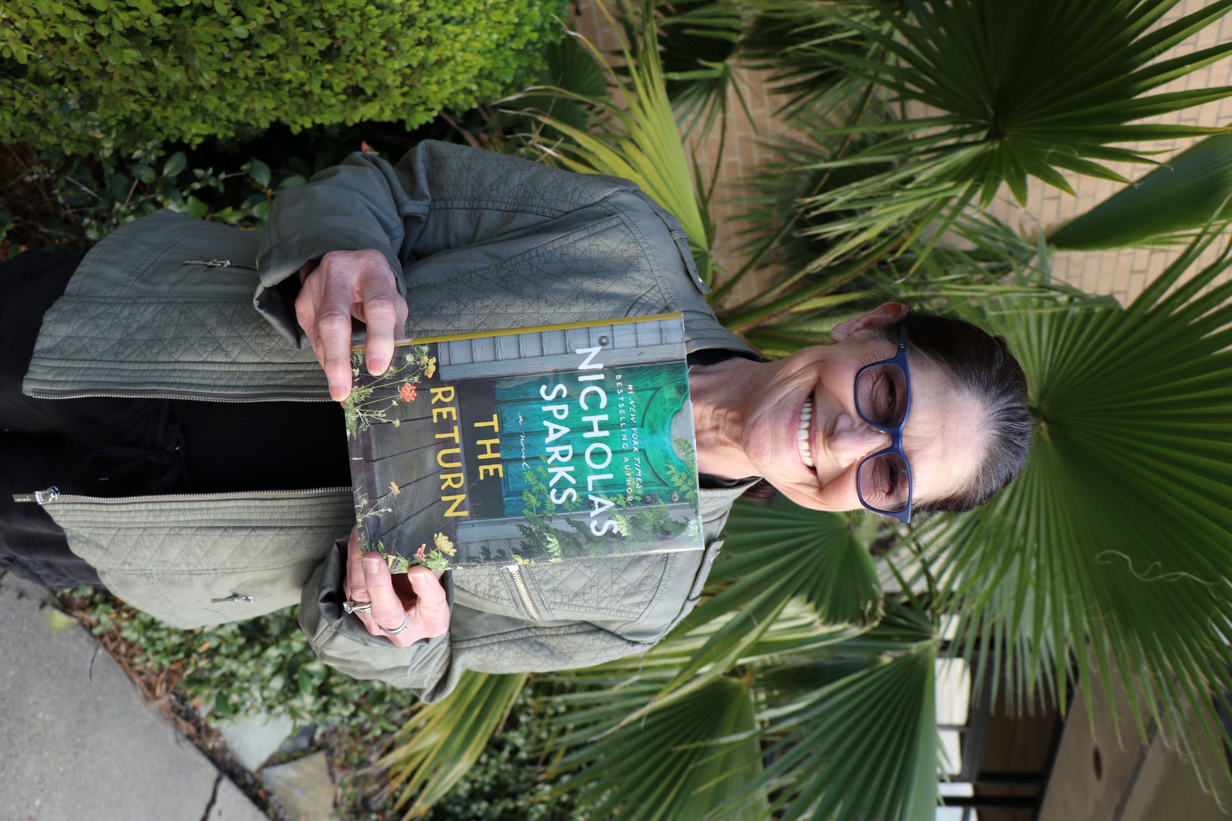 A woman stands in front of a plant. She is holding the book The Return.
