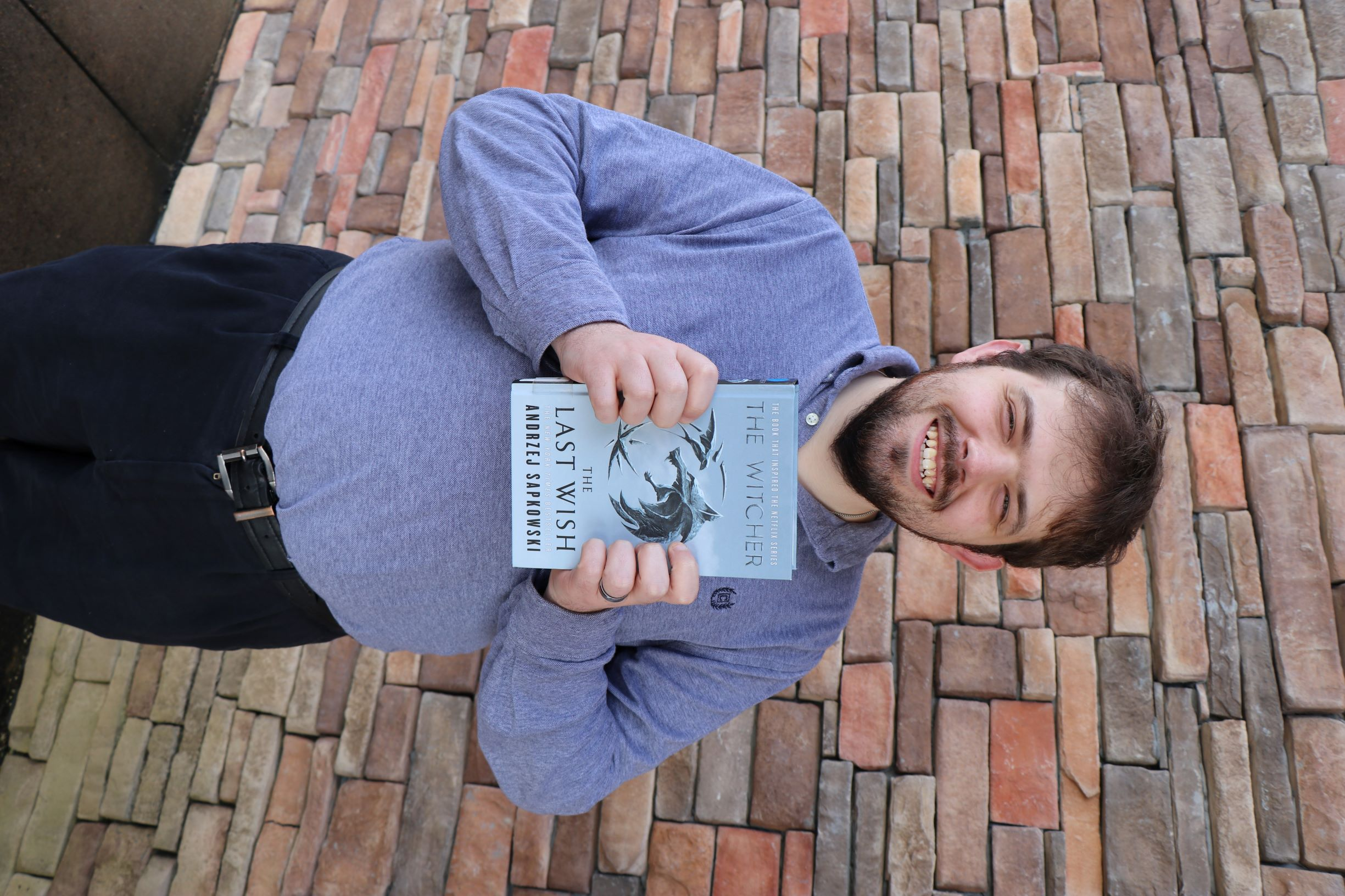 A man stands in front of a brick wall. He is holding the book The Last Wish.