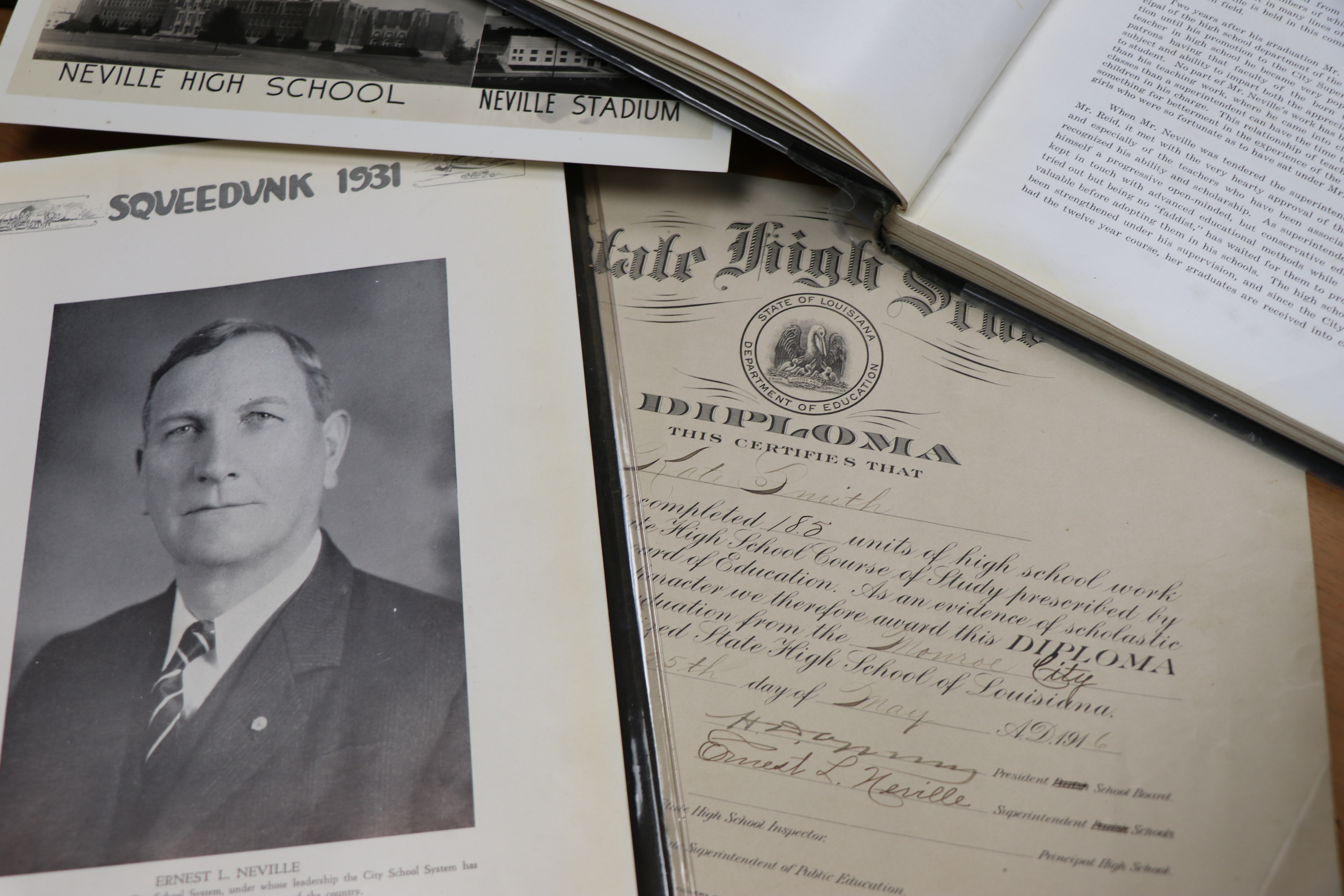 A table featuring various historical items:a 1931 Squeedunk yearbook open to a portrait of Ernest Long Neville, a high school diploma, and more