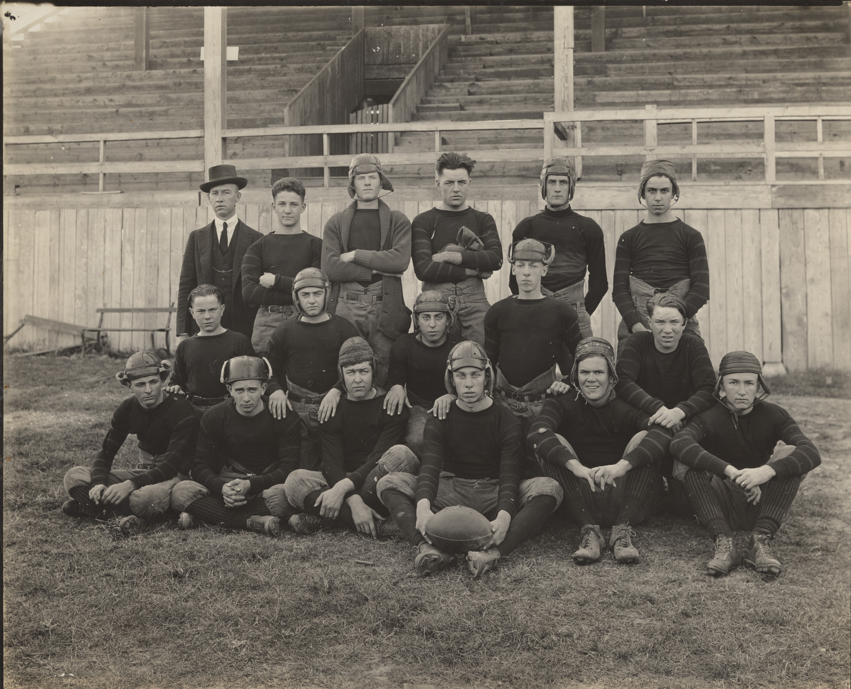 A black and white image of teenage boys in old school football uniforms. The boys pose on a field.