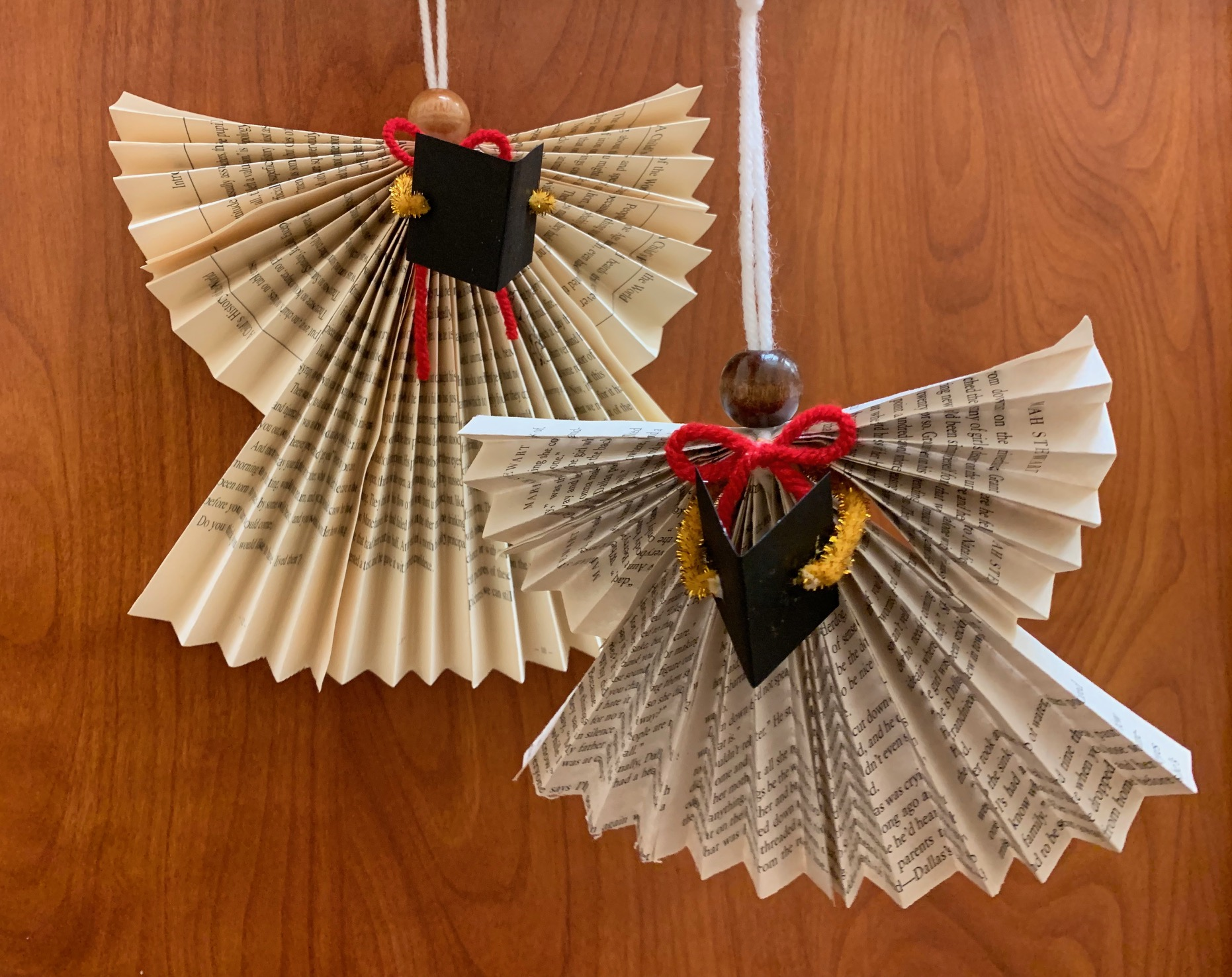 Two Christmas ornaments hang. They are carolers made out of book pages.