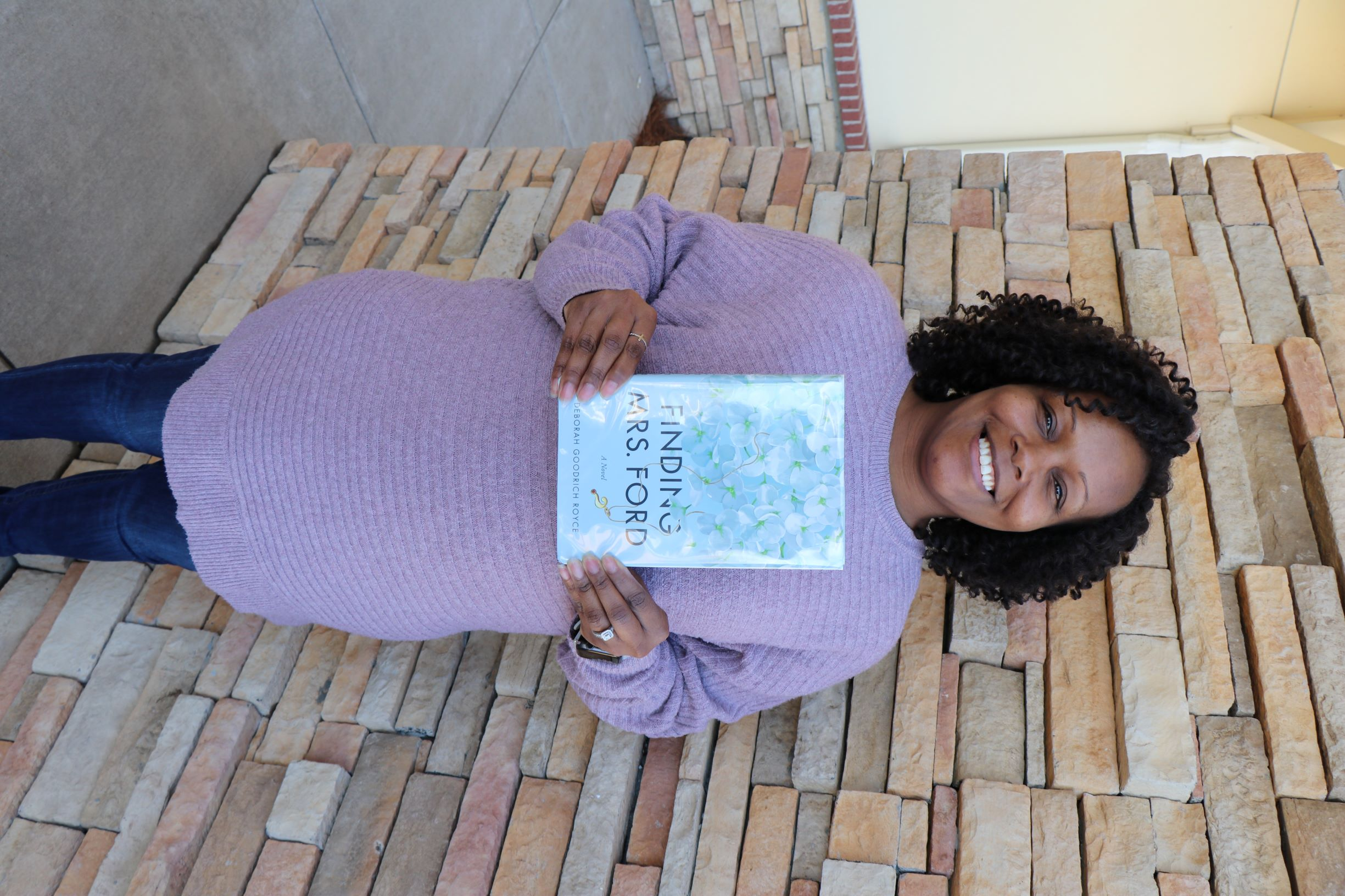 A woman stands in front of a brick wall. She is holding the book Finding Mrs. Ford