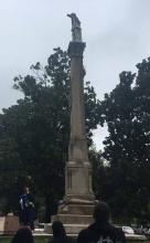 Image of speaker and Saunders Monument in Monroe City Cemetery