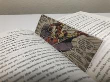 A comic bookmark is in place in the middle of a book.